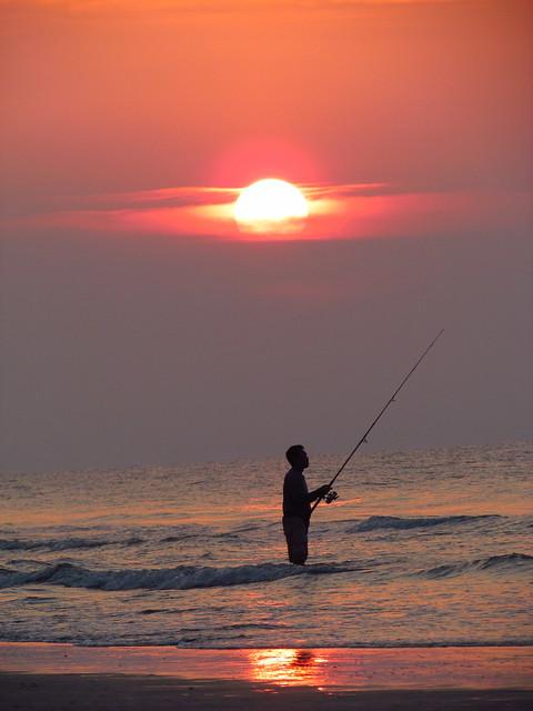Man surf fishing at sunrise in hilton head island south c for Hilton head surf fishing