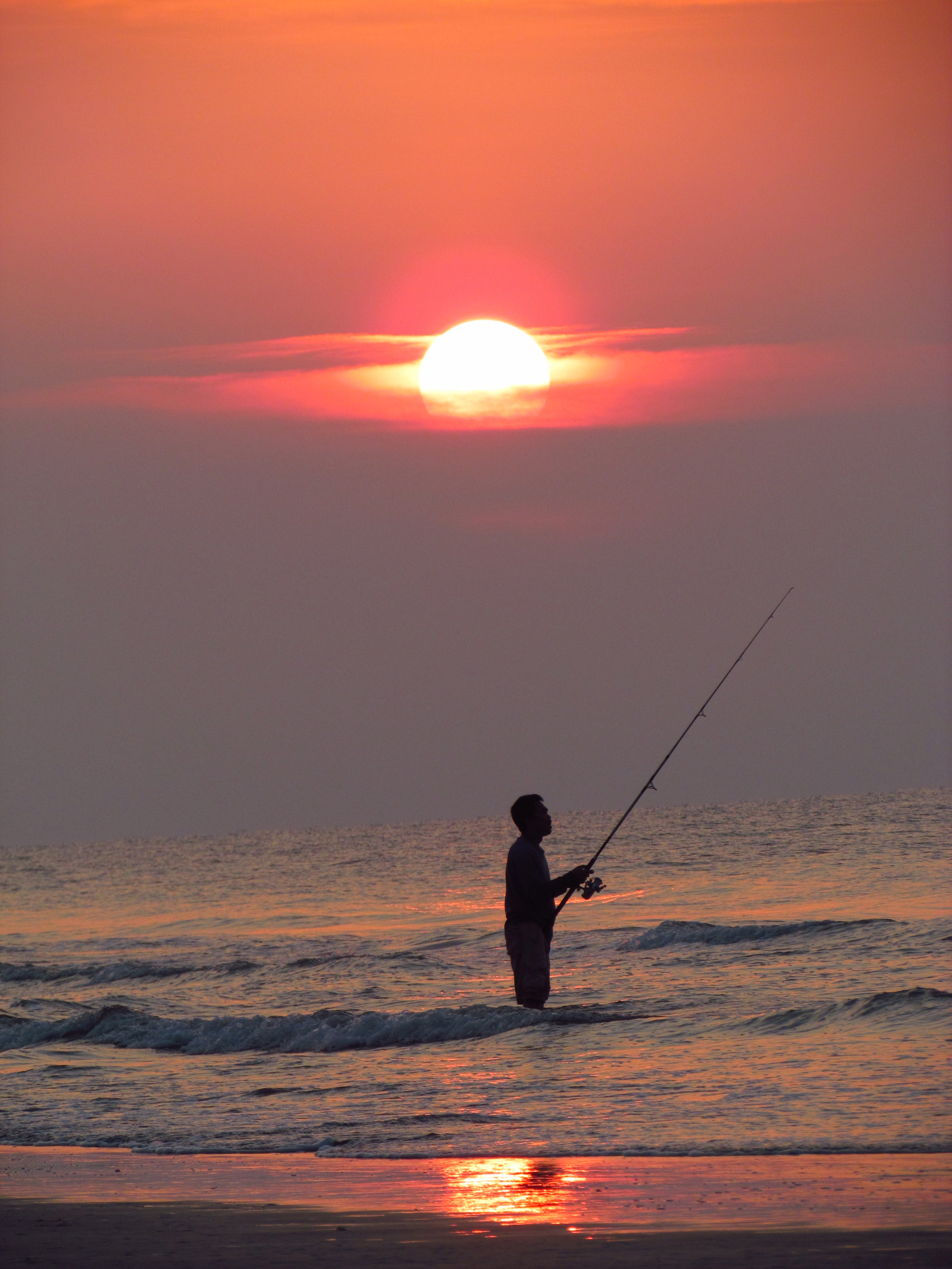 Man surf fishing at sunrise in hilton head island south for South carolina surf fishing