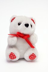 White fluffy teddy bear with red bow