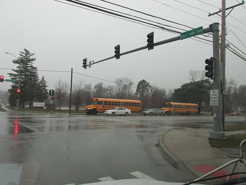 Two southbound school buses passing by in the rain on Greenwood Road at West Lake Avenue.  Glenview Illinois.  Early December 2013. by Eddie from Chicago