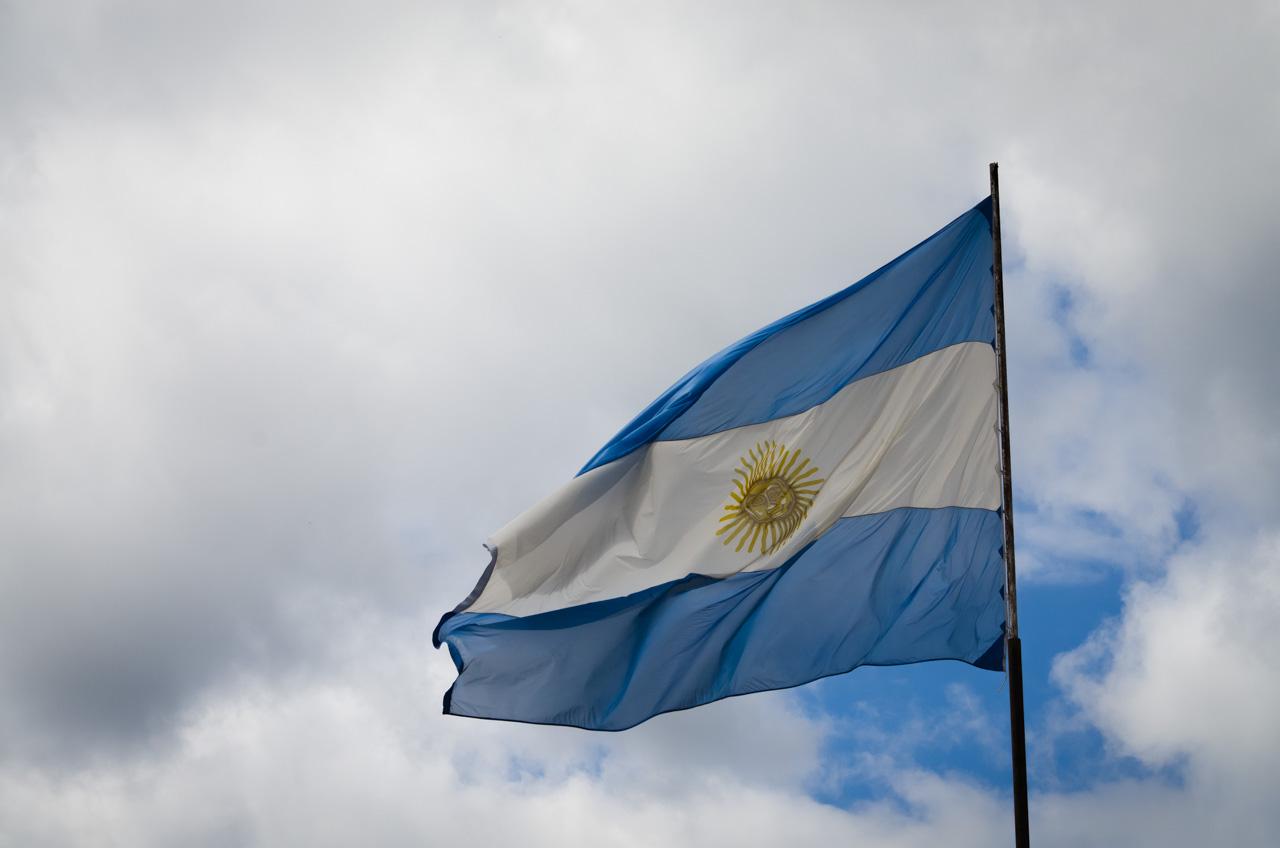 La bandera la nación argentina flamea frente a la entrada del Parque Nacional Iguazú, que representa el mayor centro turístico de Misiones, Argentina. (Elton Núñez).
