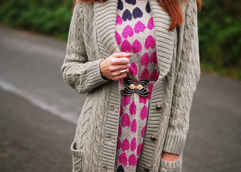 Long cable knit cardigan layered over patterned dress