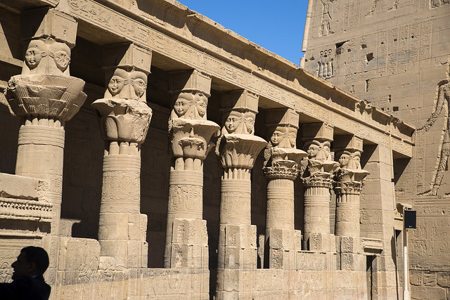 Temple at Philae: A colonnade surrounds three sides of the birth-house, with floral column capitals surmounted by sistrum capitals with Hathor heads.