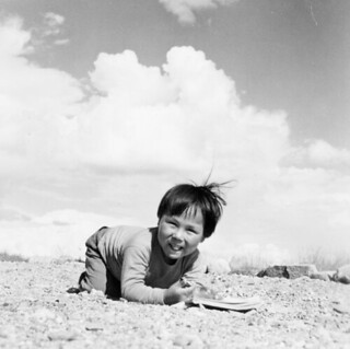 Young Inuk kneeling on the ground and smiling, Qamanittuaq, Nunavut / Le jeune Inuk agenouillé sur le sol et souriant, à Qamanittuaq (Nunavut)
