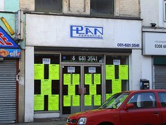 "A plain-looking terraced shopfront with its surround painted white.  A sign above reads ""Plan Personnel"" in a logo-like design.  The shopfront is fully glazed, but the view into the interior is blocked by 20 neon-yellow A4-sized posters stuck to the window in groups of five.  Each poster has writing on it advertising a different job. A red car is parked outside the shop."