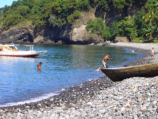 Boats and rocky volcanic beach on island of Flores West Timor. Half naked men swimming.