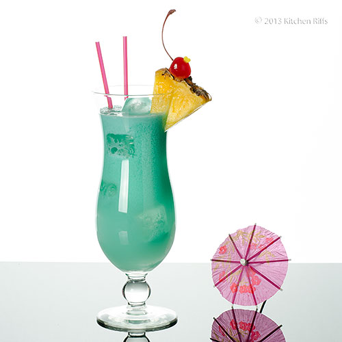 Blue Hawaii Cocktail garnished with pineapple and maraschino cherry