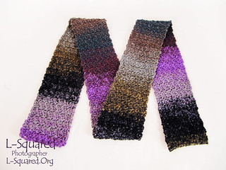 Roughly textured scarf crocheted from yarn that fades from sections of black gray, lilac, plum, moss green, dark teal, and brown.