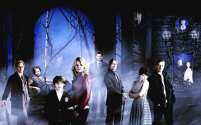 The all-white cast of Once Upon a Time stands in a shadowy forest.