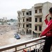 A Syrian girl waves from the balcony of an unfinished apartment block in northern Lebanon