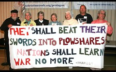 Seven plowshares activists seen together at the Pax Christi event Sunday. They are holding a sign created by the late Philip Berrigan, who participated in the first action in 1980. (Photos courtesy of Ted Majdosz)