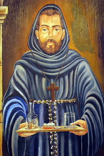 Hooded bearded monk carrying water and medicine, wood cross, blue robes, paint on wood panel, The fountain of the archangel Saint Michael, La Fonda de San Miguel Arcangel, Guadalajara, Mexico by Wonderlane