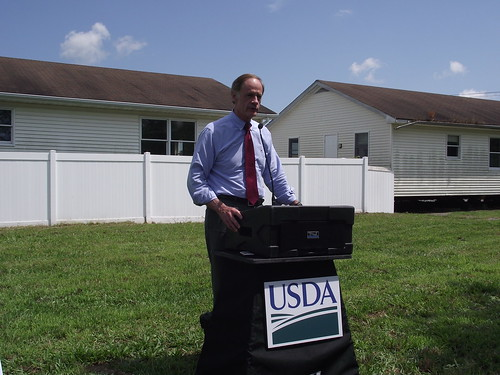 Senator Carper speaks at an event in Georgetown, Del., to highlight a USDA grant award that will help renovate the modular buildings behind him into a permanent home for Primeros Pasos (First Steps) early care and learning center. USDA photo.