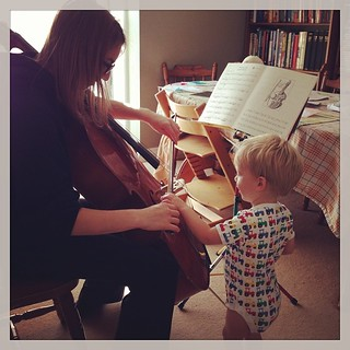Feeling the music by bowing in the cello with big sister.