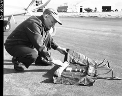 1954. W.J. Buckhorn shows survival gear pack worn during aerial detection surveys. Hillsboro Airport, OR.