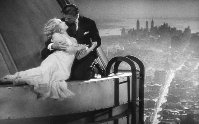 A little love happening on top of the brand new Empire State Building. 5th Avenue, the classic skyline of Lower Manhattan, Brooklyn at left and Staten Island in the distance. New York. 1932