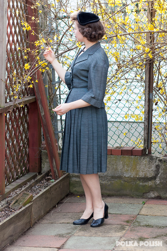 Early 1950s suit in black and slate with pleated skirt, large lucite buttons, and short wide sleeves.  Paired with black pumps and a black hat with velvet pom pom trim