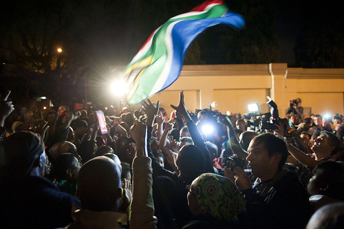 South Africans celebrate the life of former ANC leader and President Nelson Mandela outside his home on December 5, 2013. Millions are mourning him throughout the country. by Pan-African News Wire File Photos