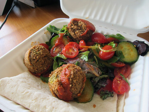 To-go container filled with a big slice of folded lavash bread, three falafel balls, and a salad.