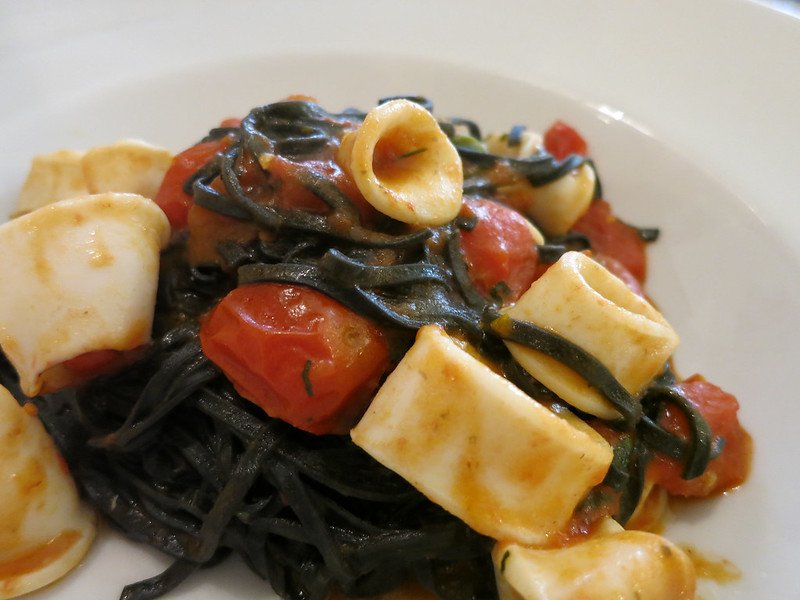 Squid ink pasta with squid and tomatoes.