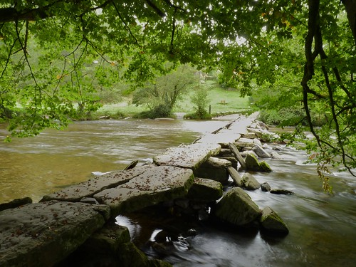 The River Barle flowing quickly through the medieval clapper bridge of Tarr Steps
