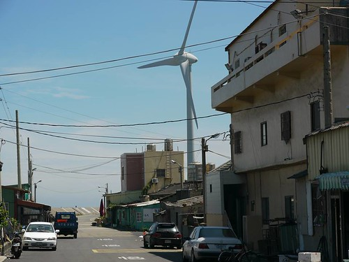 許多設立於台灣的風機與民宅距離超近,日夜運轉的低頻噪音和光影,嚴重影響居民生活品質和健康。圖為台中地區離民宅很近的風機,攝影:宋竑廣。