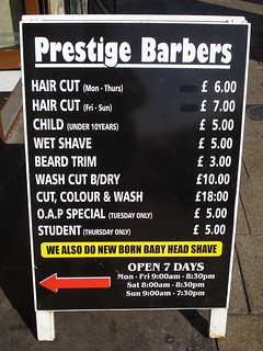A-board giving prices of various haircuts and shaves, as well as opening hours. The text is in white on a black background. A large red arrow at the bottom points toward the shop.
