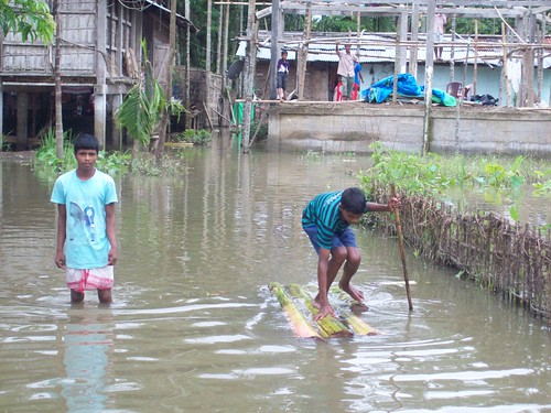 Bamboo rafts being used during floods; The houses on 'stilts' in the background have survived the floods