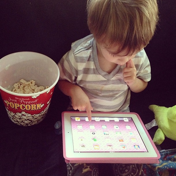This morning with Riley. Popcorn for breakfast, playing the cool games on big sister's iPad, and his toki doki dinosaur.