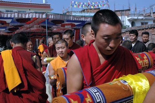 Thoughful Tibetan Buddhist Monks, Offerings: Buddhist rugs,Thangkas, silken katags, in line to present to the lama HH Jigdal Dagchen Sakya, leity, conclusion Sakya Lamdre, Tharlam Monastery, Boudha, Kathmandu, Nepal by Wonderlane