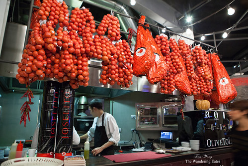 Various tomatoes and jamon hanging over a section of the bar