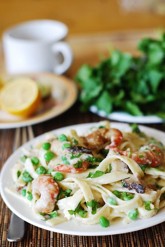 Healthy fettuccine alfredo with cauliflower sauce, shrimp, mushrooms, and sweet peas