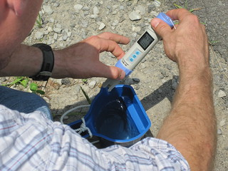 Calebe using a conductivity meter showing 873 on Tripple S Creek