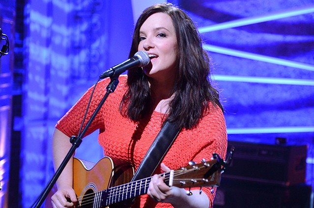 Brandy Clark, a white singer with brown hair and a guitar