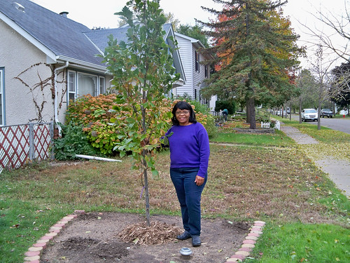 Frogtown homeowner Renee Taylor stands proudly next to her newly planted tree thanks to the tree planting partnership. (U.S. Forest Service/Teri Heyer)
