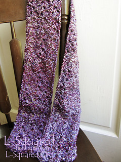 Completed scarf draped over the back of a wooden chair