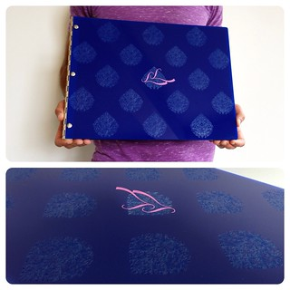 Custom graphic design portfolio book in blue acrylic with engraving and vinyl decal treatment