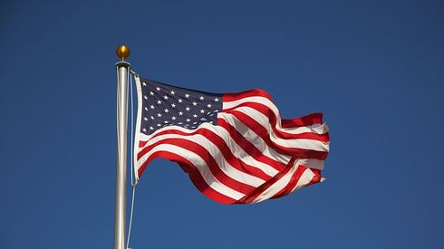American flag on pole waving in breeze