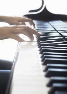 Photo of two hands playing a piano keyboard
