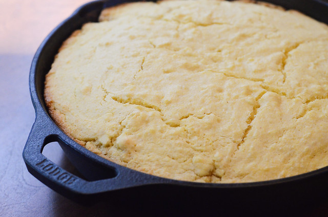 A close up of cornbread in a cast iron skillet.