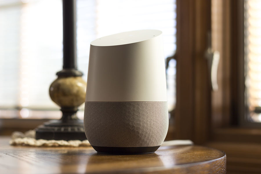 Google Home on table in front of sunny window.
