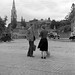 Man talking to woman in cobbled square, church visible in background, Co. Dublin by National Library of Ireland on The Commons