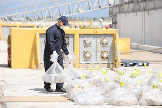 A crewmember stationed aboard the Coast Guard Cutter Forward places a bag of seized cocaine along with the rest Friday, September 20, 2013, at Naval Station Mayport, Fla. The drugs were seized by a a Coast Guard Law Enforcement Detachment stationed aboard the U.S. Navy Oliver Hazard Perry-class frigate USS Rentz (FFG-46) approximately 300 miles north of the Galapagos Islands. U.S. Coast Guard photo by Petty Officer 3rd Class Anthony L. Soto