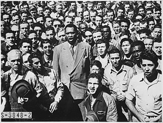 """Paul Robeson, world famous Negro baritone, leading Moore Shipyard [Oakland, CA] workers in singing the Star Spangled Banner...09/1942"