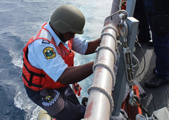A Republic of Nauru police officer climbs down USS Kidd's accommodation ladder to embark its rigid-hull inflatable boat and conduct a boarding of a fishing vessel within Nauru's economic exclusive zone, Jan. 26. (U.S. Navy photo by LS2 Karolina Brooks)