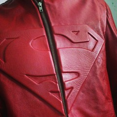 textile(0.0), maroon(0.0), hood(0.0), pocket(0.0), leather jacket(1.0), clothing(1.0), red(1.0), sleeve(1.0), leather(1.0), outerwear(1.0), jacket(1.0), zipper(1.0),