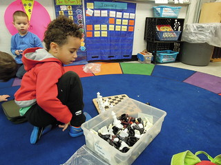 a pre-k student at PS 261 contemplates a tub of chess pieces