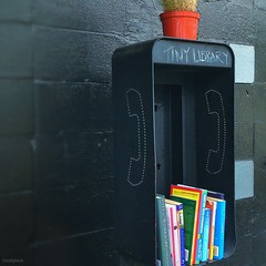 Pay phone booth repurposed as a free library / tiny library