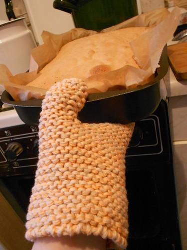 прихватка ставит бисквит на плиту