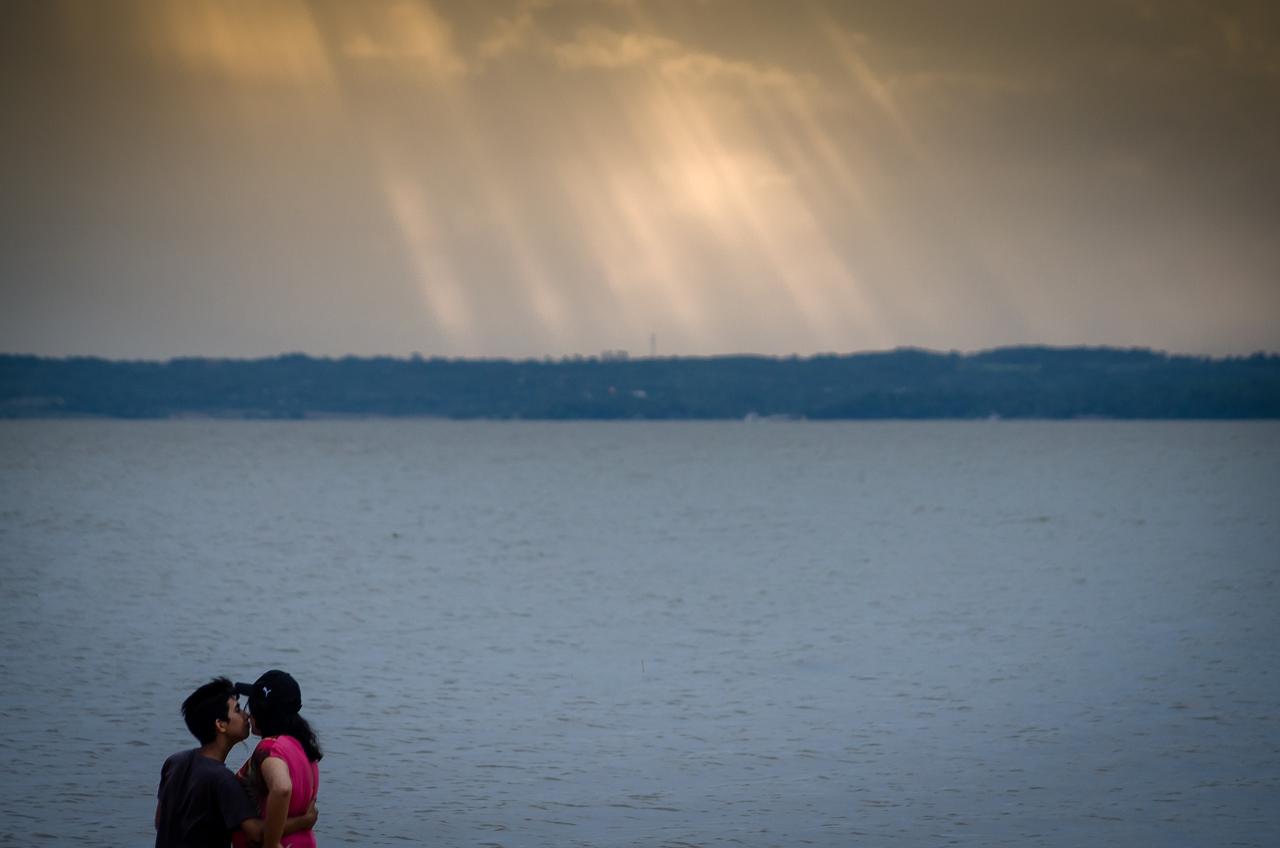 Una pareja disfruta del atardecer en la orilla del río Paraná en la playa San José de la ciudad de Encarnación. (Elton Núñez).